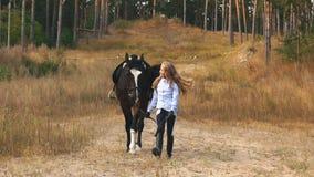 Mała dziewczynka chodzi w jesień lesie wraz z koniem zdjęcie wideo