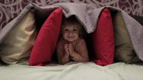 Mała dziewczynka chuje pod koc i poduszkami na łóżku Pojęcie kryjówka zbiory