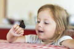 Mała dziewczynka chwyty na ręce Aglais io zegarki dla on i motyl, obserwacja, emocje Zdjęcie Royalty Free