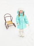 Mała dziewczynka ciągnie jej saneczki w zima dniu Obraz Royalty Free