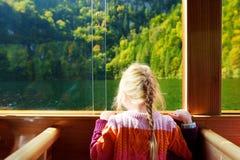 Mała dziewczynka cieszy się widok głęboki - zieleń nawadnia Konigssee podczas gdy podróżujący elektryczną łodzią Konigsee zna jak Zdjęcia Royalty Free