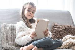Mała dziewczynka czyta książkę na wygodnej kanapie, piękne emocje fotografia stock
