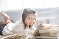 Mała dziewczynka czyta książkę na wygodnej kanapie, piękne emocje zdjęcie stock