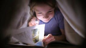 Mała dziewczynka czyta książkę pod koc z latarką w ciemnym pokoju przy nocą zbiory
