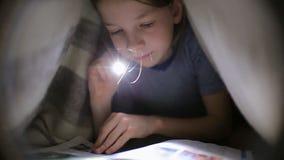 Mała dziewczynka czyta książkę pod koc z latarką w ciemnym pokoju przy nocą zbiory wideo