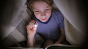 Mała dziewczynka czyta książkę pod koc z latarką w ciemnym pokoju przy nocą zdjęcie wideo