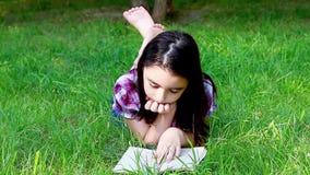 Mała dziewczynka czyta książkę w lato parku zbiory wideo