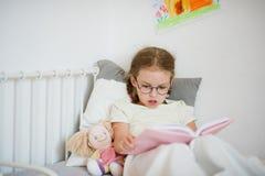 Mała dziewczynka czyta książkę w szkłach podczas gdy kłamający w łóżku Zdjęcie Stock