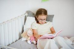 Mała dziewczynka czyta książkę w szkłach podczas gdy kłamający w łóżku Obrazy Stock