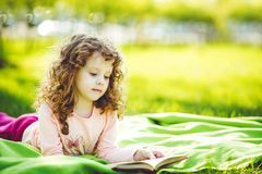 Mała dziewczynka czyta książkę w wiosna parku, Zdjęcie Stock