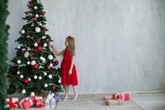 Mała dziewczynka dekoruje choinka nowego roku wakacje domu prezenty obraz stock