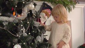 Mała dziewczynka dekoruje choinki zbiory wideo