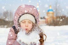 Mała dziewczynka dmucha śnieg z mitynkami zdjęcia stock