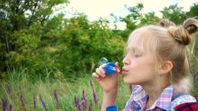 Mała dziewczynka dmucha mydlanych bąble na zielonym gazonie zbiory wideo