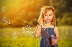 Mała dziewczynka dmucha mydlanych bąble w naturze Zdjęcie Royalty Free