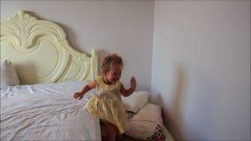 Mała Dziewczynka Dokazuje skoki zestrzela Białego łóżko poduszki na podłoga zbiory wideo