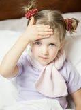 Mała dziewczynka dotyka jej czoło fotografia stock