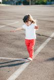 Mała dziewczynka działająca na drodze daleko od Zdjęcie Stock