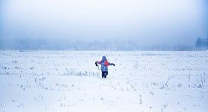 Mała dziewczynka działająca w śnieżnym parku daleko od Fotografia Royalty Free