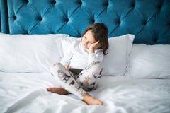 Mała dziewczynka dzieciak kłaść na łóżku z telefonem komórkowym i ogląda kreskówki obrazy royalty free