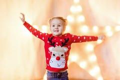 Mała dziewczynka dzieciak w czerwonym puloweru doskakiwaniu, ono uśmiecha się przeciw y i obrazy royalty free