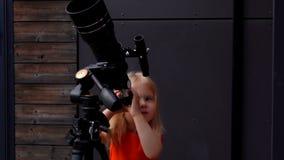 Ma?a dziewczynka egzamininuje niebo przez teleskopu zdjęcie wideo