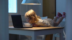 Mała dziewczynka entuzjastycznie ogląda kreskówki na laptopu lying on the beach na stole zdjęcie wideo