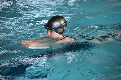 Mała dziewczynka flatteru ćwiczy kopnięcie z kopnięcie deską w salowym pływackim basenie Obraz Stock