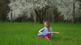 Mała dziewczynka gitarzysta bawić się sola siedzący w cudownej miejsce melodii twój gitarę na tle kwitnie drzewna zielona trawa j zbiory