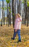 Mała dziewczynka iść daleko od na dywanie złoci jesień liście fotografia royalty free