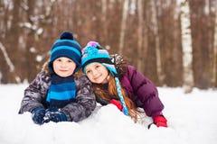 Mała dziewczynka i chłopiec kłamamy w pobliżu na snowdrift obrazy stock
