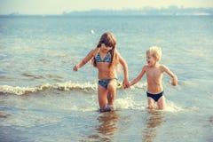 Mała dziewczynka i chłopiec w morzu Zdjęcia Royalty Free