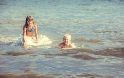 Mała dziewczynka i chłopiec w morzu Obrazy Stock