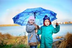 Mała dziewczynka i chłopiec z parasolem bawić się w deszczu Dzieciaki bawić się plenerowego dżdżystą pogodą w spadku Jesieni zaba Zdjęcie Stock