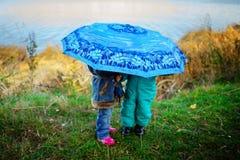 Mała dziewczynka i chłopiec z parasolem bawić się w deszczu Dzieciaki bawić się plenerowego dżdżystą pogodą w spadku Jesieni zaba Obrazy Royalty Free