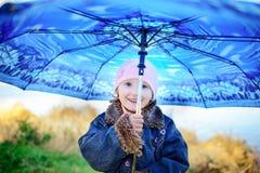 Mała dziewczynka i chłopiec z parasolem bawić się w deszczu Dzieciaki bawić się plenerowego dżdżystą pogodą w spadku Jesieni zaba Fotografia Stock