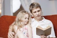 Mała dziewczynka i ojciec cieszymy się czytelniczą książkę wpólnie Obrazy Stock