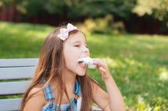 Mała dziewczynka je bawełnianego cukierku obsiadanie na ławce w parkowym lecie obrazy royalty free