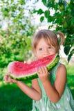 Mała dziewczynka je dużego plasterka arbuza w parku w zieleni sukni fotografia royalty free