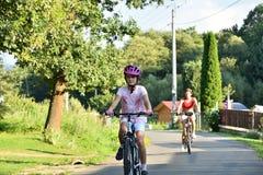 Mała dziewczynka jechać na rowerze z jej matką jako aktywność sport na fury drodze zdjęcia royalty free
