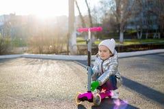 Ma?a dziewczynka jedzie hulajnog? w parku na Pogodnym wiosna dniu Aktywny czas wolny i plenerowy sport dla dzieci zdjęcie royalty free