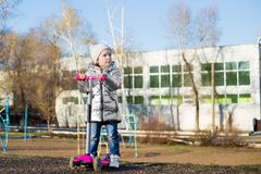 Ma?a dziewczynka jedzie hulajnog? w parku na Pogodnym wiosna dniu Aktywny czas wolny i plenerowy sport dla dzieci zdjęcie stock