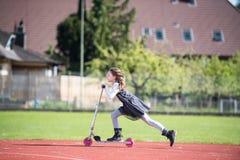 Mała dziewczynka jedzie hulajnoga na sport łatwości Obrazy Royalty Free