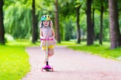 Mała dziewczynka jedzie kolorową hulajnoga fotografia stock