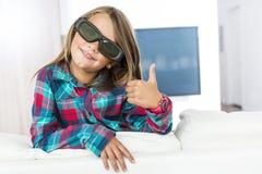 Mała dziewczynka jest ubranym 3D szkła i ogląda telewizję Zdjęcia Royalty Free
