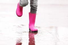 Mała dziewczynka jest ubranym gumowych buty bryzga w kałuży na deszczowym dniu, ostrość nogi fotografia stock