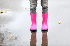 Mała dziewczynka jest ubranym gumowych buty stoi w kałuży zdjęcia stock