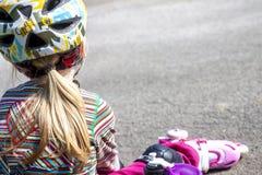 Mała dziewczynka jest ubranym ostrzy siedzieć i łasowanie i pije wodę mineralną obraz stock