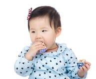 Mała dziewczynka kąska zabawki blok Obrazy Stock