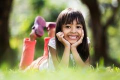 Mała dziewczynka kłaść na zieleni ziemi Obrazy Stock